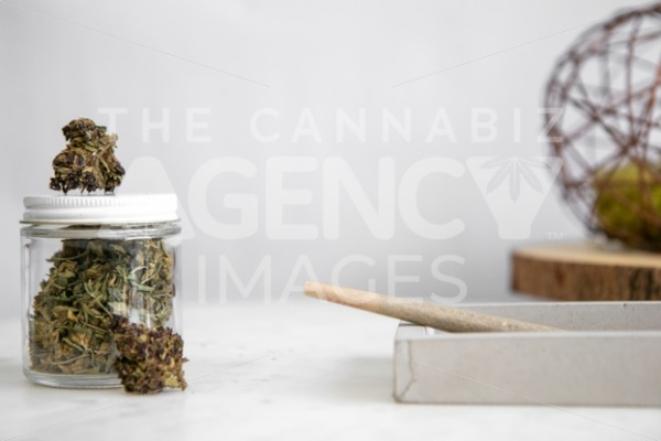 Flower Bud in Glass Jar with Roll on White Marble 3 - Cannabis Royalty Free Stock Images